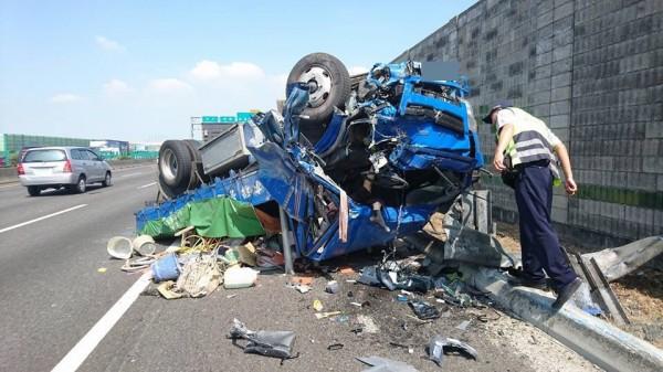 小貨車撞上掉落在車道上的鐵齒輪後失控撞上護欄翻護。(截圖自台灣新聞記者聯盟資訊平台)