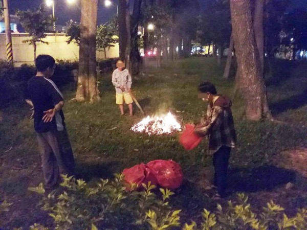 三男於公園草地上燒金紙。(記者陳文嬋翻攝)