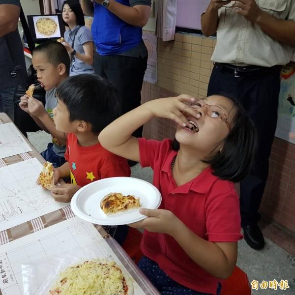 尚仁國小學生自製海派披薩一拿到手,迫不及待的吃了起來,學生吃了一直說好吃,忍不住說感謝SEAFOOD。(記者俞肇福攝)