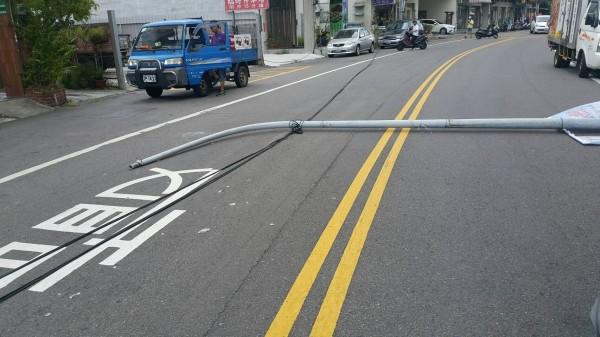 路燈桿倒地,橫躺路面。(記者彭健禮翻攝)