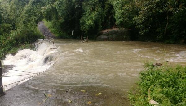 礁溪跑馬古道猴洞坑溪溪水爆漲,已越過路面,衝毀護欄。(記者江志雄翻攝)