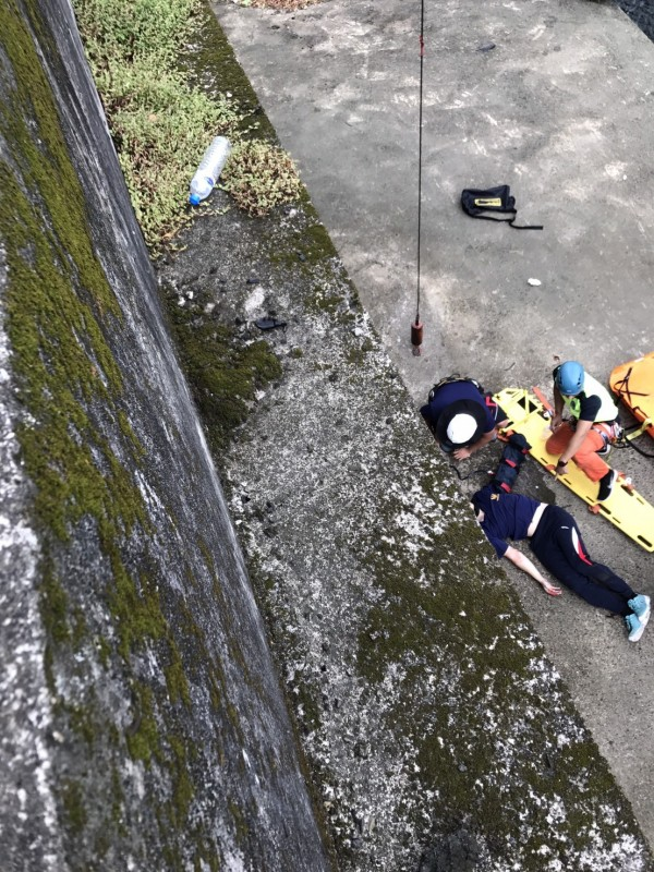 新竹縣政府消防局第二大隊常訓,陳姓隊員疑不慎踩到青苔,自5公尺高的平台跌落水溝邊。(記者廖雪茹翻攝)