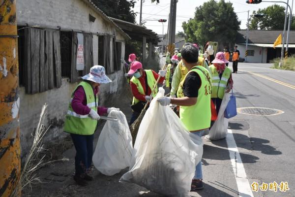 環保志工在強風、艷陽下賣力掃街。(記者黃淑莉攝)