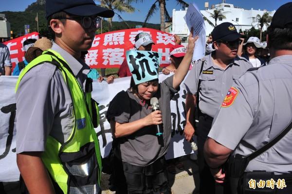 縣議員蔣月惠(舉手者)在現場拉起布條大聲呼籲「抗議墾丁轉運站、交通打結大壞蛋」。(記者蔡宗憲攝)