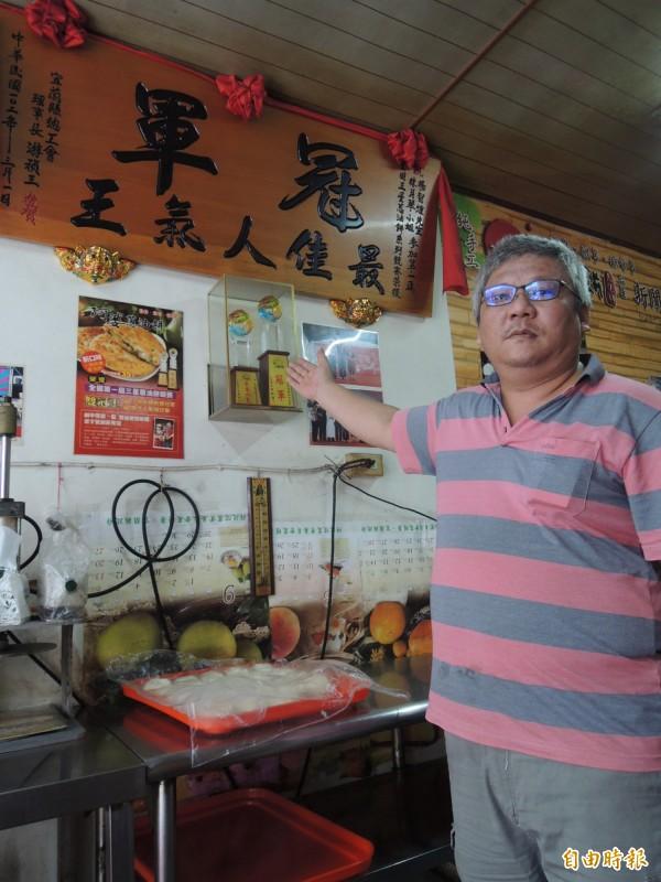 第二代掌門人楊智煌,指著牆上冠軍匾額,訴說阿婆蔥油餅的輝煌歷史。(記者江志雄攝)