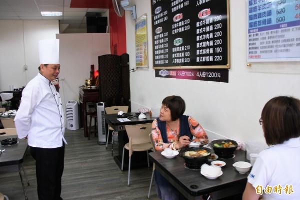 海濱養生鍋料好實在且價格平實,讓民眾一試成主顧,詢問何明坤(左)打包回家如何料理。(記者林欣漢攝)