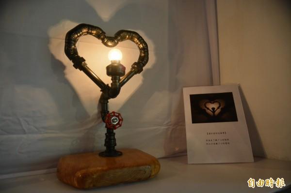 希瓿·瓦硌以愛為主題設計「鐵了心的愛妳」系列工業風鐵件作品,利用光影投射出愛心光影。(記者王峻祺攝)