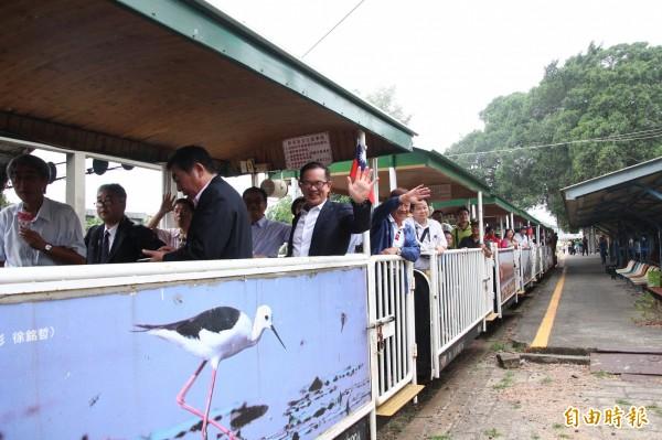 遊客們開心在車廂內向外揮手。(記者林宜樟攝)