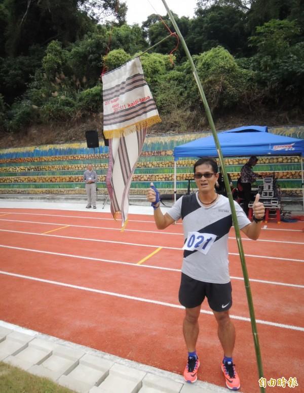 走鏢冠軍朱瑞欽,在特別設計的冠軍旗下高興合照。(記者張勳騰攝)
