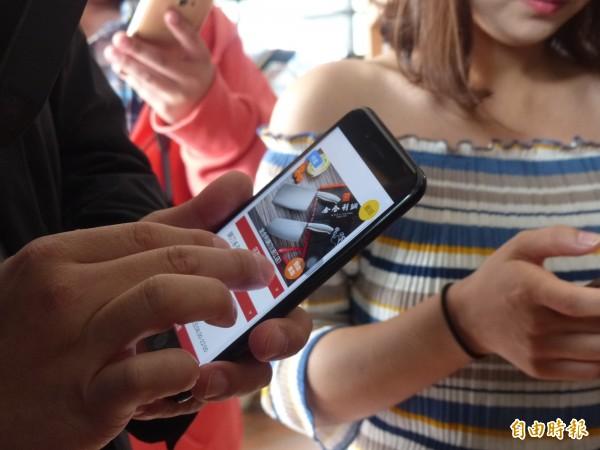 金門購物節啟動,已有不少民眾開始使用手機下載「金門智慧商圈聰明購」APP,率先接收好康訊息。(記者吳正庭攝)