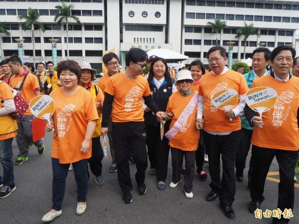 桃園市長鄭文燦前著90多歲長者的手一起路跑一小段。(記者陳昀攝)