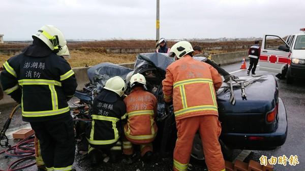 自小客車嚴重變形,女駕駛卡在其中消防人員積極搶救。(記者劉禹慶攝)