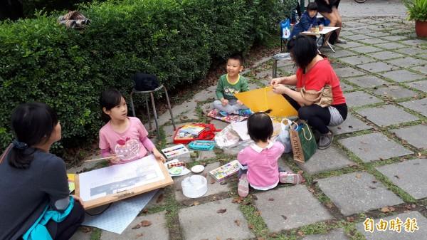 小朋友坐在地磚上,眼觀教堂、提筆作畫。(記者黃明堂攝)