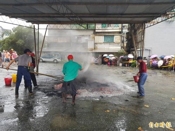 現場炭火超過150度高溫,工作人員事先用粗鹽降溫,避免發生意外。(記者俞肇福攝)