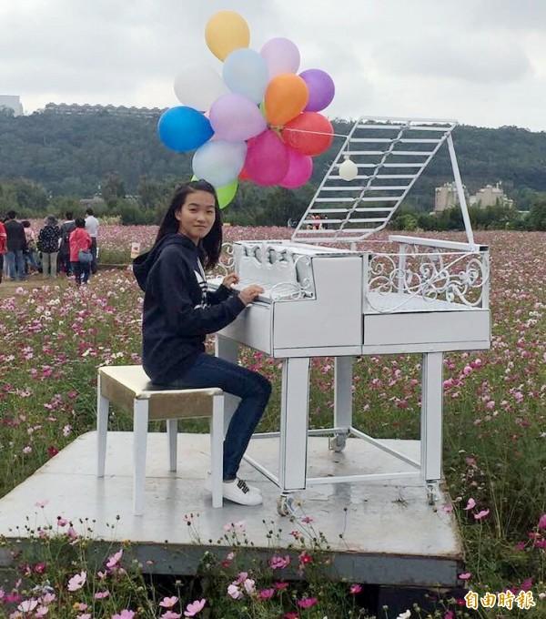 龍潭花區亮眼的白色鋼琴。(記者李容萍攝)