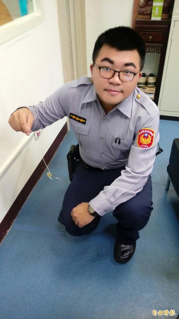 警員劉立夫用用磁鐵組幫助胡姓男子撿回鑰匙。(記者周敏鴻攝)