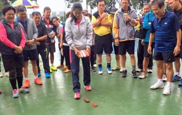 南投縣魚池鄉三藏杯軟式網球錦標賽,12日社會男女團體組賽程,因雨受阻,最後以「擲筊」聖杯數多寡決定輸贏,吸引大家圍觀。(記者謝介裕翻攝)(記者謝介裕攝)