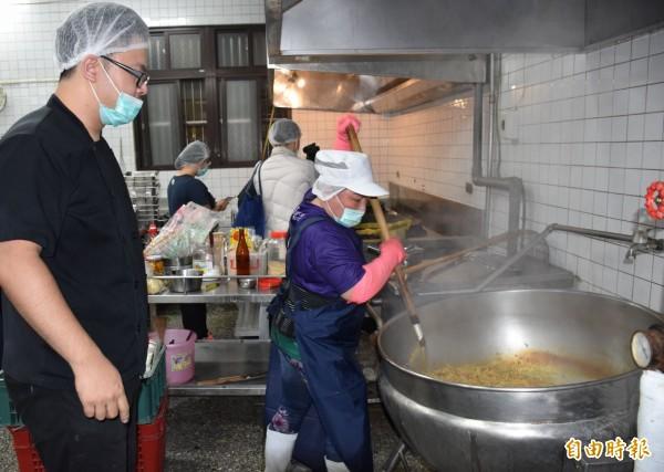 洪昭勝(左)走進青埔國小營養午餐廚房,第一線指導廚工們「分段料理」的祕訣。(記者李容萍攝)