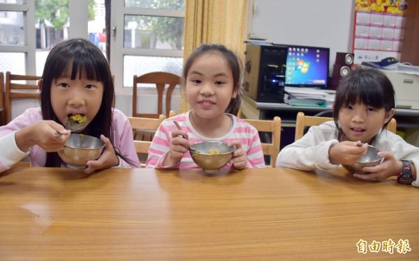 使用南瓜、紅蘿蔔、香菇、碗豆等烹飪的黃金蘿蔔糕,成了取代傳統米飯的主食,3位小女生試吃都說好吃。(記者李容萍攝)