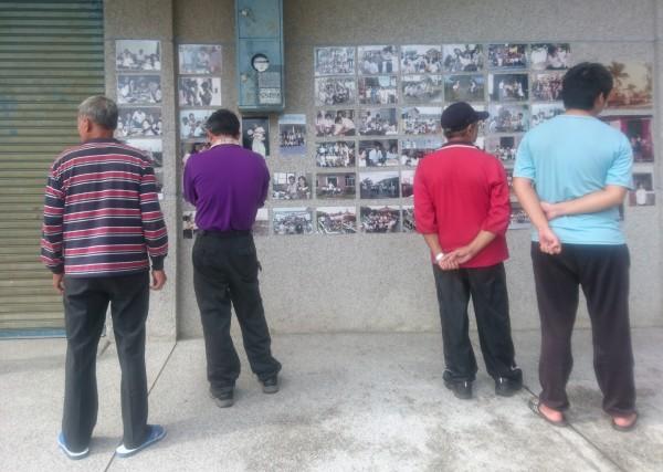 榮光村民對著照片牆一一瀏覽,並與旁人細數過去。(記者陳冠備翻攝)
