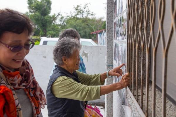 榮光村當地耆老,來到照片牆,開心回憶時光。(邱明憲提供)