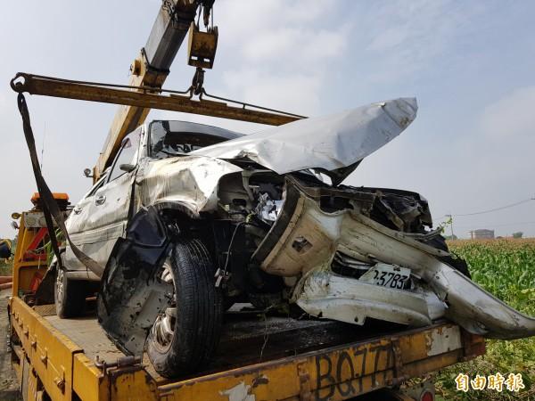 休旅車疑因車速過快追撞前車後,衝下邊坡翻落玉米田,毀損的車頭慘不忍睹。(記者王涵平攝)
