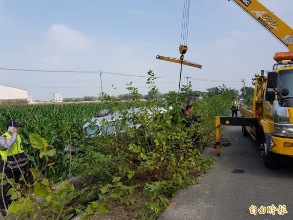 大型拖吊車正設法將休旅車從玉米田拖出。(記者王涵平攝)