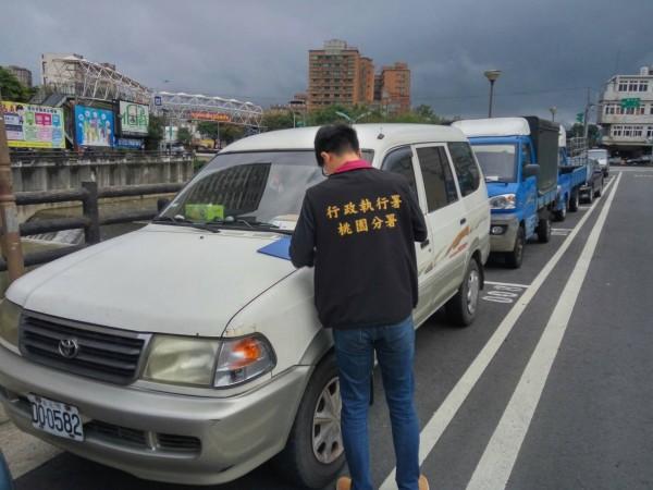 桃園分署、交通局合作執法,今天在蘆竹區錦溪街查扣、拖吊長期欠費的車輛。(桃園分署提供)