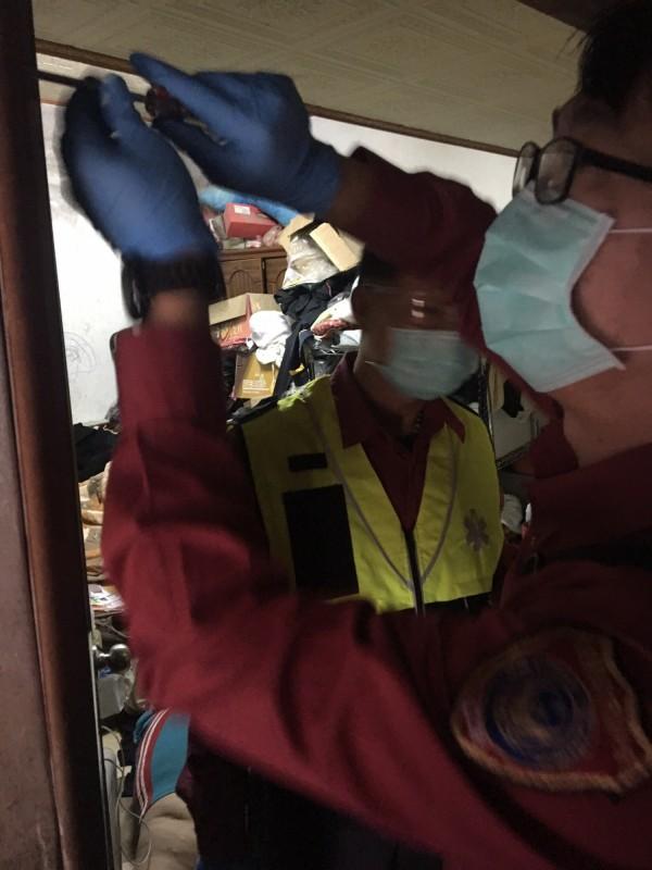 消防人員用螺絲起子拆除張男房間門板,以利搬運救護。(記者彭健禮翻攝)