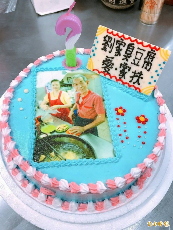 基隆家扶中心準備劉清山夫妻賣臭豆腐的照片在蛋糕上,祝福劉清山生日快樂,讓劉清山夫妻很感動。(記者俞肇福攝)