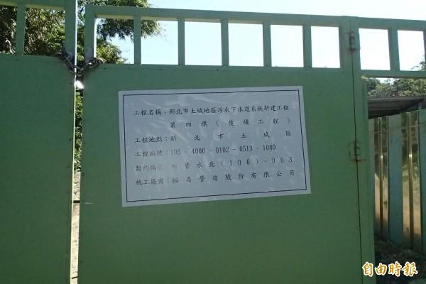 大門貼有污水下水道工程告示牌。(記者余衡攝)