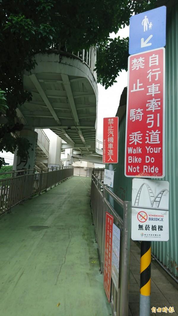 牽引道入口標示「禁止騎乘」,但仍有民眾騎車上下行。(記者何玉華攝)