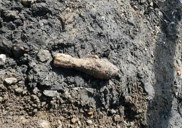 國立興大附中大門前東榮路今天上午施工時,挖出一顆疑似軍方60迫砲彈未爆彈。(記者陳建志翻攝)