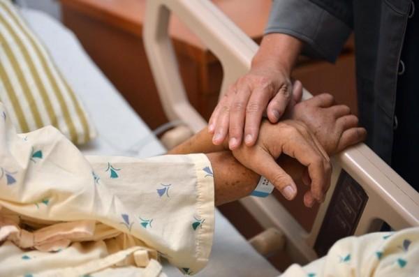 花媽前往醫院探望戴振耀時,握著耀伯的手。(翻攝臉書)