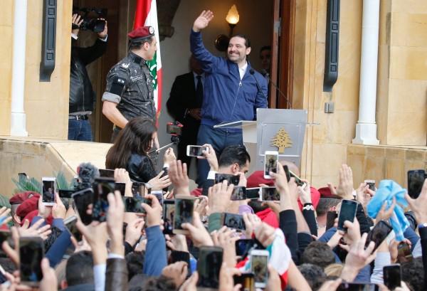 同意暫緩辭職的黎巴嫩總理哈里里22日在位於首都貝魯特的自宅外向大批支持者揮手致意。(路透)