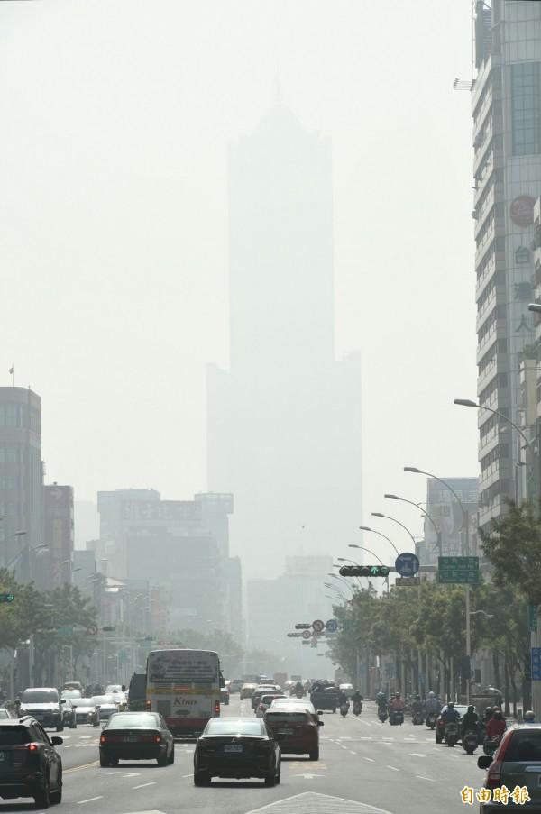 高雄冬季的空氣品質差,地標85大樓今天幾乎消失不見。(記者張忠義攝)