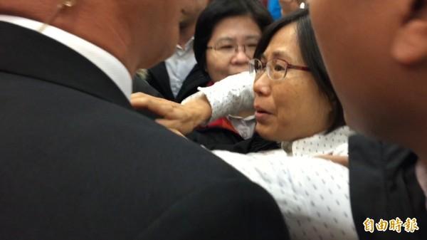 自稱公民團體成員的劉曉蕙闖入會場遞交「反亞泥還我土地自救會」陳情書。(記者王峻祺攝)