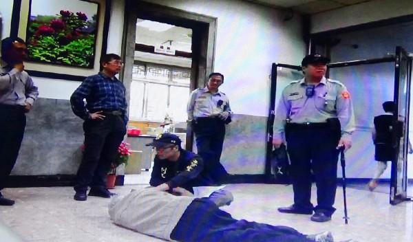 老翁生氣地躺在銀行地上。(中興警分局提供)