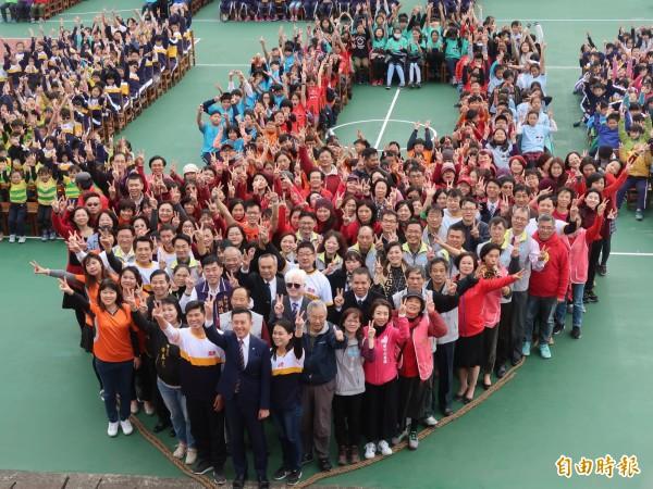新竹市南寮國小的三座運動場大翻修後,今天啟用。學生和家長排出100的數字,祝賀學校明年100歲。(記者洪美秀攝)