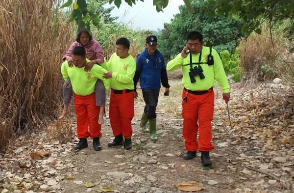 江姓婦人(左)獲救後體力透支,有輕微脫水現象,由救難人員揹負脫困。(圖:神鷹山區搜救隊提供)