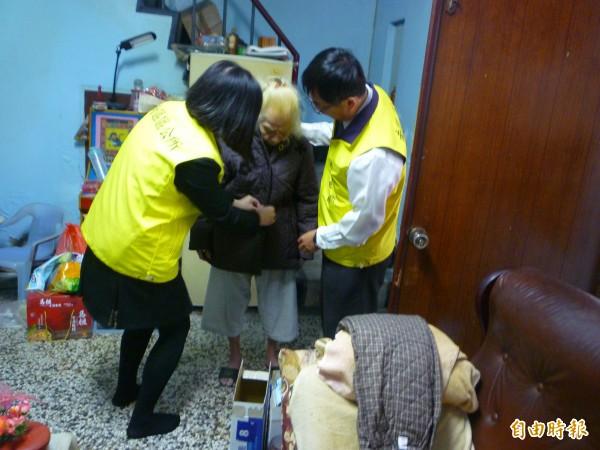 南區區長朱棟(右一)到獨居老人家中送禦寒用的棉被與冬衣。(記者王俊忠翻攝)