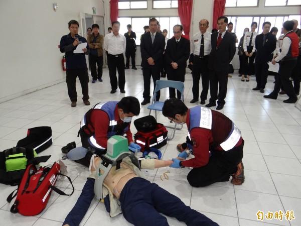 消防救護員以自動心肺復甦機(在患者身上)模擬對患者急救情境。(記者王俊忠攝)