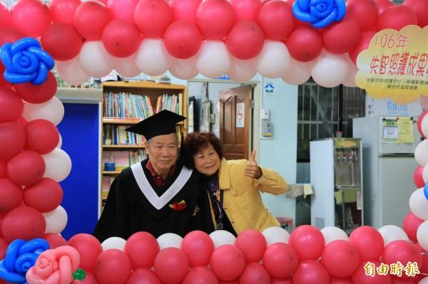 阿公穿著學士服,開心的在氣球門框邊拍畢業照。(記者鄭名翔攝)