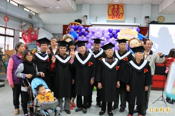 共照中心的阿公、阿婆們穿著學士服,開心拍畢業照。(記者鄭名翔攝)