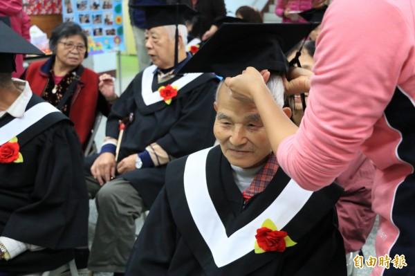 工作人員親切的幫即將畢業的阿公戴上學士帽。(記者鄭名翔攝)
