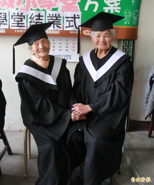 90歲的楊陳收蓮(左)與90 歲的謝嬉容(右),闊別80年再當同學,今日一起攜手畢業。(記者陳冠備攝)