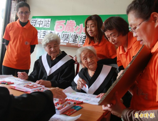 謝嬉容(左)與楊陳收蓮(右),闊別80年再當同學,一起讀書識字,重溫當學生樂趣。(記者陳冠備攝)