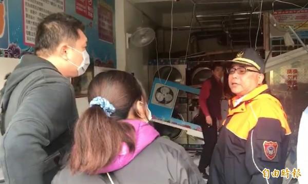自助洗衣店業者與消防調查人員,進入意外現場接受調查。(記者陳冠備翻攝)