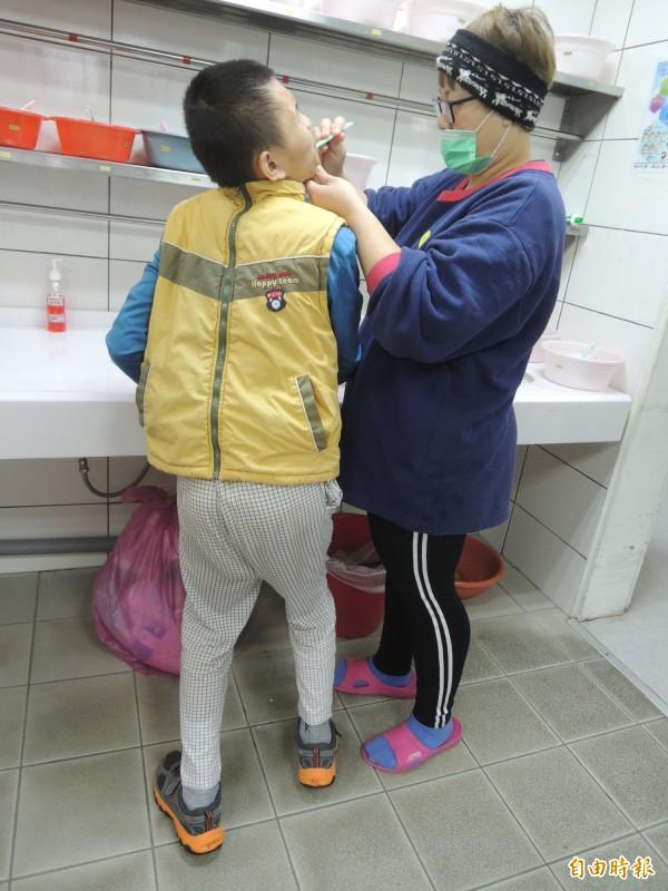 經由世光教養院的專業照顧,加上親情的支持,腦性麻痺的翔翔從完全不能走,到現在可以自己走路,進步驚人。圖為工作人員協助翔翔刷牙。(記者廖雪茹攝)