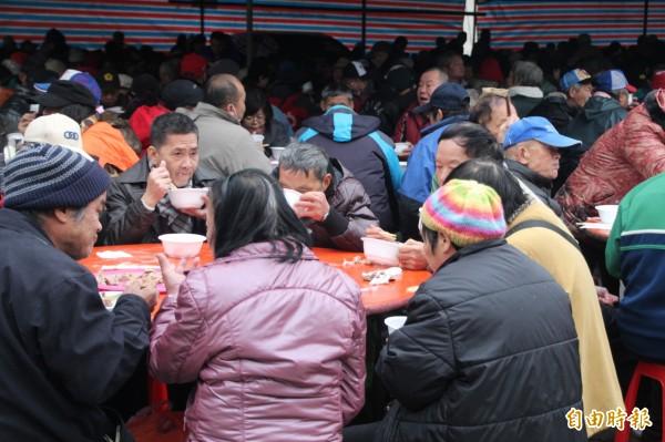 廖榮吉長年在萬華發送便當跟舉辦「街友宴」,從一開始請五桌,到最多曾經請過一千桌以上,往年都會有蝦子、豬腳及無限量的愛心麵,讓街友也能感受年夜飯。(資料照,記者鍾泓良攝)